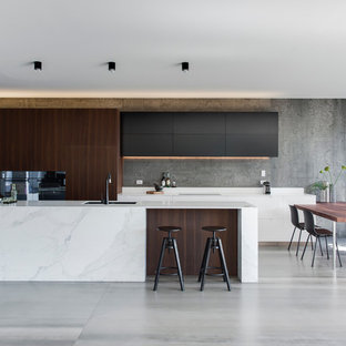 Design ideas for a mid-sized modern galley eat-in kitchen in Sydney with dark wood cabinets, solid surface benchtops, grey splashback, cement tile splashback, ceramic floors, with island and an undermount sink.