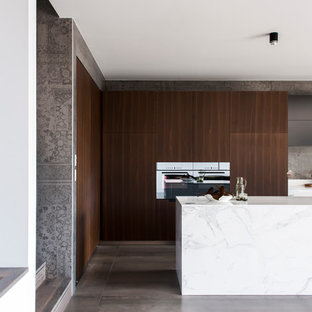 Design ideas for a mid-sized modern l-shaped eat-in kitchen in Sydney with an integrated sink, dark wood cabinets, solid surface benchtops, grey splashback, cement tile splashback, black appliances, ceramic floors and with island.