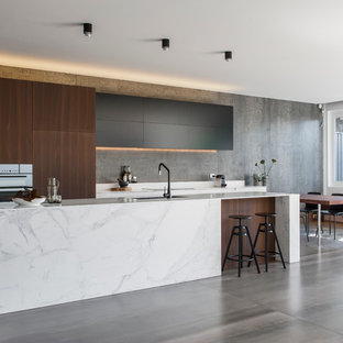 This is an example of a mid-sized modern l-shaped eat-in kitchen in Sydney with an integrated sink, dark wood cabinets, solid surface benchtops, grey splashback, cement tile splashback, black appliances, ceramic floors and with island.