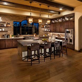 タンパの大きい地中海スタイルのおしゃれなアイランドキッチン (人工大理石カウンター、レンガのキッチンパネル、シルバーの調理設備の、無垢フローリング、茶色い床、アンダーカウンターシンク、シェーカースタイル扉のキャビネット、濃色木目調キャビネット) の写真