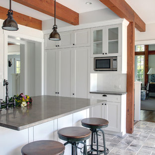 This is an example of a large traditional u-shaped eat-in kitchen in Manchester with stainless steel appliances, limestone benchtops, an undermount sink, shaker cabinets, white cabinets, white splashback, subway tile splashback, travertine floors and with island.