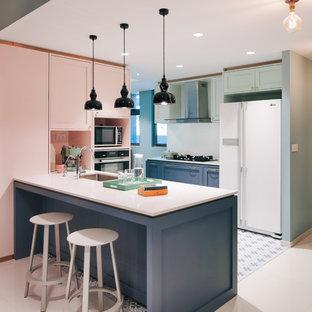 シンガポールのエクレクティックスタイルのおしゃれなキッチン (アンダーカウンターシンク、シェーカースタイル扉のキャビネット、緑のキャビネット、白い調理設備、青い床、白いキッチンカウンター) の写真