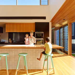Photo of a contemporary kitchen in Brisbane with flat-panel cabinets, medium wood cabinets, wood benchtops, black splashback, glass sheet splashback, stainless steel appliances, light hardwood floors, with island and beige floor.