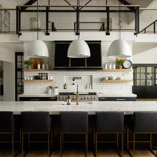 Offene Landhaus Küche in L-Form mit Landhausspüle, flächenbündigen Schrankfronten, schwarzen Schränken, Küchenrückwand in Weiß, Rückwand aus Metrofliesen, Küchengeräten aus Edelstahl, braunem Holzboden, Kücheninsel, braunem Boden, weißer Arbeitsplatte und gewölbter Decke in Boise