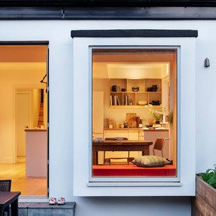 Bild på ett stort minimalistiskt grå grått kök, med en integrerad diskho, släta luckor, vita skåp, laminatbänkskiva, vitt stänkskydd, stänkskydd i stenkakel, rostfria vitvaror, bambugolv, en köksö och gult golv