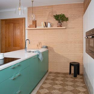 他の地域の小さい北欧スタイルのおしゃれなキッチン (フラットパネル扉のキャビネット、珪岩カウンター、セラミックタイルの床、ベージュの床、白いキッチンカウンター、アンダーカウンターシンク、黒い調理設備、ターコイズのキャビネット) の写真