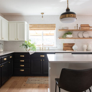 Farmhouse kitchen remodeling - Kitchen - farmhouse l-shaped light wood floor and brown floor kitchen idea in Seattle with shaker cabinets, black cabinets, stainless steel appliances, an island, white countertops, white backsplash and subway tile backsplash
