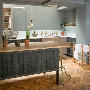 ロンドンの中サイズのインダストリアルスタイルのおしゃれなL型キッチン (大理石カウンター、無垢フローリング、アンダーカウンターシンク、フラットパネル扉のキャビネット、ヴィンテージ仕上げキャビネット、白いキッチンパネル、石スラブのキッチンパネル) の写真