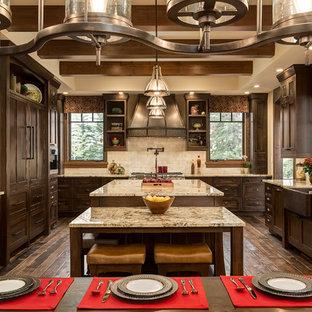 Inredning av ett rustikt stort kök, med en rustik diskho, skåp i shakerstil, skåp i mörkt trä, granitbänkskiva, beige stänkskydd, integrerade vitvaror, en köksö, mörkt trägolv och stänkskydd i travertin