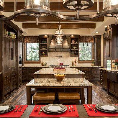 Eat-in kitchen - large rustic u-shaped dark wood floor eat-in kitchen idea in Calgary with a farmhouse sink, shaker cabinets, dark wood cabinets, granite countertops, beige backsplash, paneled appliances, an island and travertine backsplash