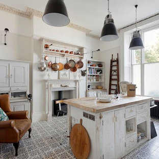 Example of a cottage chic kitchen design in Sussex with open cabinets, wood countertops and an island