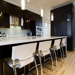 Design ideas for a contemporary kitchen in Calgary with flat-panel cabinets, dark wood cabinets and glass sheet splashback.