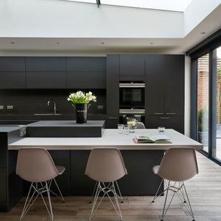Inspiration för ett funkis svart svart kök, med en nedsänkt diskho, släta luckor, svarta skåp, bänkskiva i akrylsten, svart stänkskydd, svarta vitvaror, en köksö och beiget golv