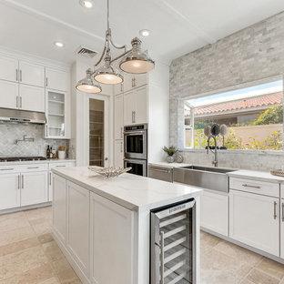 Foto på ett mellanstort vintage kök och matrum, med en rustik diskho, skåp i shakerstil, vita skåp, bänkskiva i kalksten, grått stänkskydd, stänkskydd i marmor, rostfria vitvaror, kalkstensgolv, en köksö och beiget golv