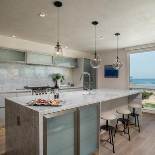 Idéer för ett stort modernt vit linjärt kök med öppen planlösning, med en undermonterad diskho, släta luckor, vita skåp, grått stänkskydd, rostfria vitvaror, ljust trägolv, en köksö, beiget golv, stänkskydd i sten och bänkskiva i kvartsit