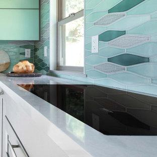 他の地域の中サイズのミッドセンチュリースタイルのおしゃれなキッチン (アンダーカウンターシンク、落し込みパネル扉のキャビネット、グレーのキャビネット、クオーツストーンカウンター、緑のキッチンパネル、セラミックタイルのキッチンパネル、パネルと同色の調理設備、淡色無垢フローリング、黄色い床、白いキッチンカウンター) の写真