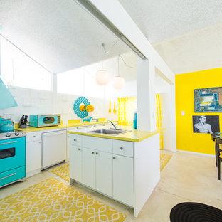 На фото: кухни в стиле ретро с обеденным столом, накладной раковиной, плоскими фасадами, белыми фасадами, белым фартуком, цветной техникой, островом, бежевым полом и желтой столешницей