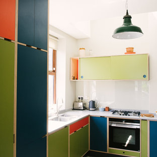 This is an example of a medium sized contemporary l-shaped kitchen in Other with a double-bowl sink, flat-panel cabinets, green cabinets, white splashback, glass sheet splashback, integrated appliances and grey worktops.