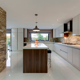 Inspiration for a large contemporary l-shaped open plan kitchen in Other with a drop-in sink, flat-panel cabinets, white cabinets, quartzite benchtops, stone tile splashback, stainless steel appliances, porcelain floors and with island.