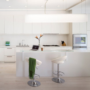 Modern kitchen pictures - Kitchen - modern l-shaped light wood floor kitchen idea in San Francisco with an undermount sink, flat-panel cabinets, white cabinets, stainless steel appliances and an island