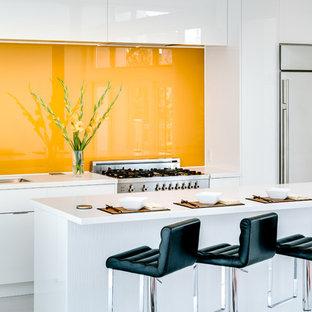 Offene, Zweizeilige Moderne Küche mit flächenbündigen Schrankfronten, weißen Schränken, Küchenrückwand in Gelb, Glasrückwand, Küchengeräten aus Edelstahl, Kücheninsel und grauem Boden in Calgary