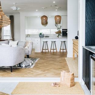 ブリスベンの小さいシャビーシック調のおしゃれなキッチン (ダブルシンク、落し込みパネル扉のキャビネット、白いキャビネット、クオーツストーンカウンター、白いキッチンパネル、黒い調理設備、無垢フローリング、茶色い床、ベージュのキッチンカウンター) の写真