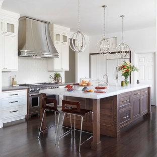 Geräumige Klassische Wohnküche in L-Form mit Unterbauwaschbecken, Schrankfronten mit vertiefter Füllung, weißen Schränken, Quarzit-Arbeitsplatte, Küchenrückwand in Weiß, Rückwand aus Keramikfliesen, Elektrogeräten mit Frontblende, dunklem Holzboden, Kücheninsel, braunem Boden und weißer Arbeitsplatte in Denver