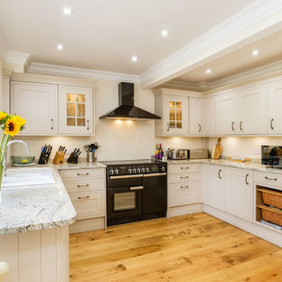 Farmhouse kitchen appliance - Example of a country u-shaped medium tone wood floor and brown floor kitchen design in New York with a drop-in sink, shaker cabinets, beige cabinets, black appliances and a peninsula