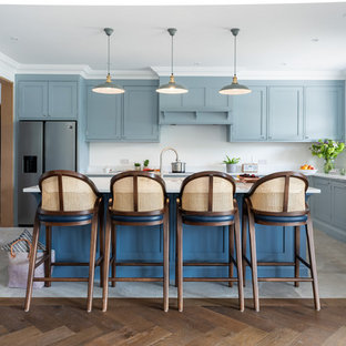 Inspiration for a large beach style u-shaped kitchen in Surrey with blue cabinets, quartzite benchtops, stainless steel appliances, ceramic floors, with island, white benchtop, shaker cabinets, white splashback and grey floor.