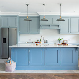 Inspiration for a large beach style u-shaped eat-in kitchen in Surrey with shaker cabinets, blue cabinets, quartzite benchtops, stainless steel appliances, ceramic floors, with island and white benchtop.