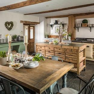 他の地域の中サイズのカントリー風おしゃれなキッチン (シェーカースタイル扉のキャビネット、白いキャビネット、カラー調理設備、黒い床) の写真