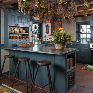Ejemplo de cocina en U, campestre, con armarios con paneles con relieve, puertas de armario azules, península y electrodomésticos de acero inoxidable