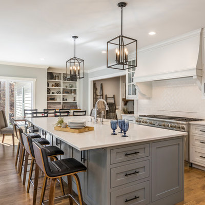 Large farmhouse l-shaped medium tone wood floor and brown floor eat-in kitchen photo in Other with a farmhouse sink, flat-panel cabinets, gray cabinets, quartzite countertops, white backsplash, ceramic backsplash, stainless steel appliances, an island and white countertops