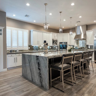 Inspiration for a large classic galley kitchen/diner in Las Vegas with a submerged sink, raised-panel cabinets, white cabinets, granite worktops, mirror splashback, stainless steel appliances, ceramic flooring, an island, grey floors and multicoloured worktops.
