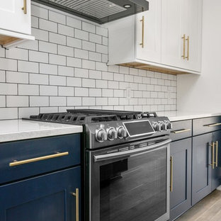 Open concept kitchen designs - Single-wall medium tone wood floor and brown floor open concept kitchen photo in Grand Rapids with a farmhouse sink, shaker cabinets, black cabinets, white backsplash, subway tile backsplash, stainless steel appliances, an island and blue countertops