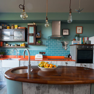This is an example of a medium sized bohemian single-wall open plan kitchen in Other with a belfast sink, flat-panel cabinets, distressed cabinets, blue splashback, ceramic splashback, porcelain flooring, an island, multi-coloured floors, wood worktops and white appliances.