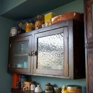 他の地域の中サイズのエクレクティックスタイルのおしゃれなキッチン (エプロンフロントシンク、フラットパネル扉のキャビネット、ヴィンテージ仕上げキャビネット、人工大理石カウンター、青いキッチンパネル、セラミックタイルのキッチンパネル、シルバーの調理設備の、磁器タイルの床、マルチカラーの床) の写真