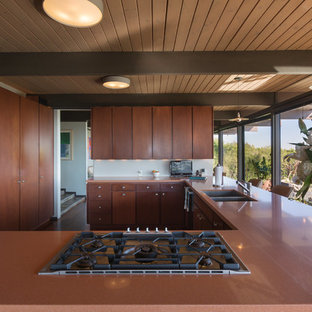 This is an example of a midcentury l-shaped open plan kitchen in Los Angeles with an undermount sink, flat-panel cabinets, medium wood cabinets, solid surface benchtops, stainless steel appliances, medium hardwood floors, a peninsula, brown floor and brown benchtop.