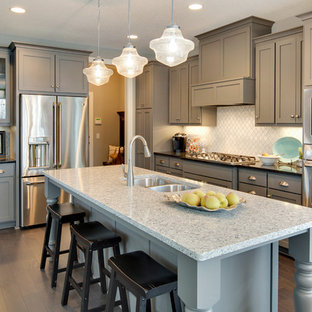 Transitional kitchen ideas - Example of a transitional l-shaped medium tone wood floor kitchen design in Minneapolis with a drop-in sink, shaker cabinets, gray cabinets, quartzite countertops, stainless steel appliances, white backsplash and an island