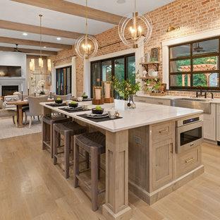 シンシナティのカントリー風おしゃれなキッチン (エプロンフロントシンク、シェーカースタイル扉のキャビネット、グレーのキャビネット、赤いキッチンパネル、レンガのキッチンパネル、シルバーの調理設備の、淡色無垢フローリング、ベージュの床、白いキッチンカウンター) の写真