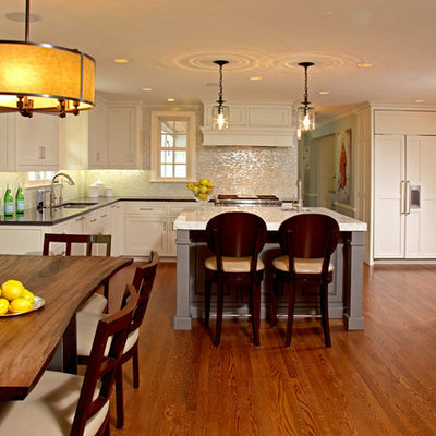 Elegant l-shaped medium tone wood floor eat-in kitchen photo in Minneapolis with marble countertops, white backsplash, paneled appliances, recessed-panel cabinets, white cabinets, a double-bowl sink and an island