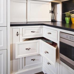Exempel på ett stort klassiskt l-kök, med luckor med infälld panel, vita skåp, bänkskiva i täljsten, svart stänkskydd, stänkskydd i sten, svarta vitvaror, mörkt trägolv och en köksö