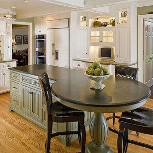 Imagen de cocina comedor en L, clásica, de tamaño medio, con encimera de esteatita, fregadero de doble seno, armarios con paneles con relieve, puertas de armario blancas, suelo de madera clara y una isla
