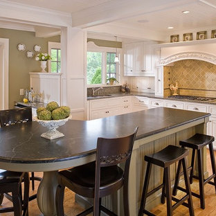 Mid-sized traditional l-shaped eat-in kitchen in Minneapolis with soapstone benchtops, a double-bowl sink, raised-panel cabinets, white cabinets, light hardwood floors and an island.