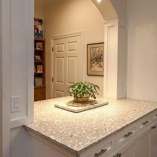 Klassisk inredning av ett mycket stort kök, med en köksö, luckor med infälld panel, vita skåp, bänkskiva i återvunnet glas, en undermonterad diskho, vitt stänkskydd, stänkskydd i keramik, rostfria vitvaror och mellanmörkt trägolv