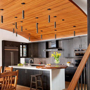 Contemporary kitchen appliance - Kitchen - contemporary l-shaped light wood floor and beige floor kitchen idea in Denver with shaker cabinets, dark wood cabinets, gray backsplash, stainless steel appliances, an island and white countertops