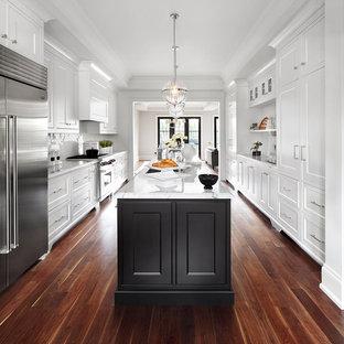 Imagen de cocina de galera, clásica renovada, con armarios con paneles empotrados, puertas de armario blancas, salpicadero blanco, electrodomésticos de acero inoxidable, suelo de madera oscura, una isla y suelo marrón