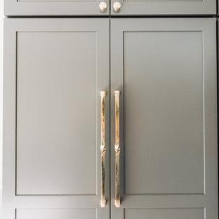 Idée de décoration pour une arrière-cuisine linéaire minimaliste de taille moyenne avec un évier encastré, un placard à porte shaker, des portes de placard grises, un plan de travail en quartz, une crédence jaune, une crédence en carreau de porcelaine, un électroménager encastrable, un sol en bois clair, un îlot central, un sol beige et un plan de travail gris.