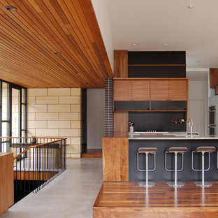 This is an example of a midcentury kitchen in Minneapolis with open cabinets, dark wood cabinets, marble benchtops, black splashback, panelled appliances and dark hardwood floors.