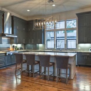 ヒューストンの大きいトランジショナルスタイルのおしゃれなキッチン (ダブルシンク、シェーカースタイル扉のキャビネット、グレーのキャビネット、クオーツストーンカウンター、メタリックのキッチンパネル、メタルタイルのキッチンパネル、シルバーの調理設備の、濃色無垢フローリング、茶色い床) の写真